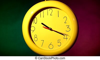 yellow clock on colorful background - close up of an yellow...