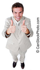 Victorious businessman with thumbs up smiling at the camera