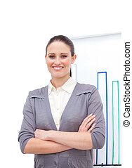 Confident young businesswoman with folded arms at a...