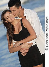 Man and Woman Couple Kissing In Romantic Embrace On Beach -...