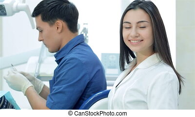 Girl-assistant smiling and  thumb up on background dentist