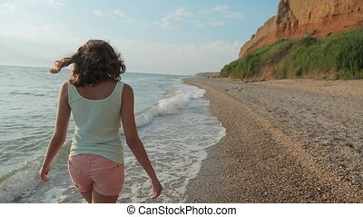 Young slim woman walking along a deserted seashore in the...