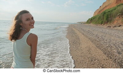 Pretty smiling girl walking on the rocky pebble beach near...