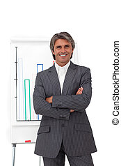 Charismatic mature businessman with folded arms in front of...