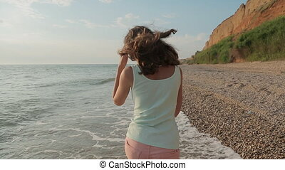 Charming smiling girl walking on sea water along the seashore in a summer