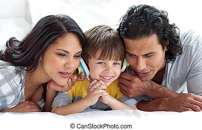Joyful parents listening to music with their son on a bed