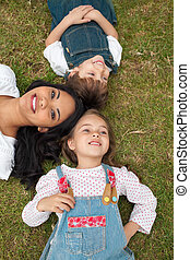 Happy mother and her children lying on the grass in a park