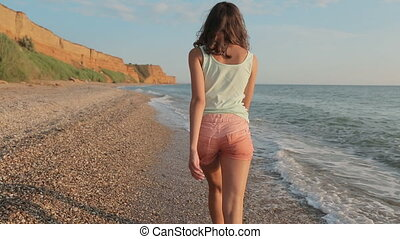 Cute girl walking along the shore and making air-kissing -...