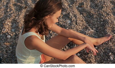 Smiling girl sitting on the beach pebbles