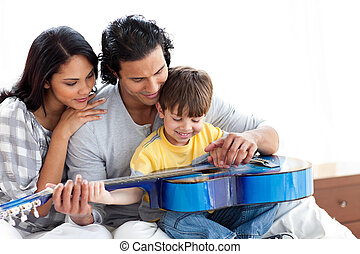 Happy little boy playing guitar with his parents at home