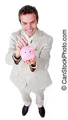 Cheerful businessman saving money in a piggybank