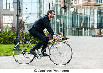 Going everywhere by his bike. Side view of young businessman...