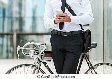 Staying in touch. Close-up of young businessman holding...