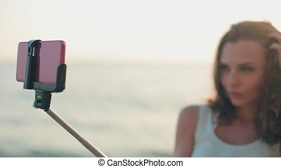 Attractive girl standing in the sea with a monopod and makes selfie to the phone