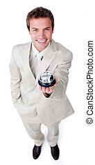 Assertive young businessman holding a service bell against a...