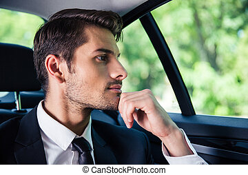 usinessman riding in car - Handsome businessman riding in...