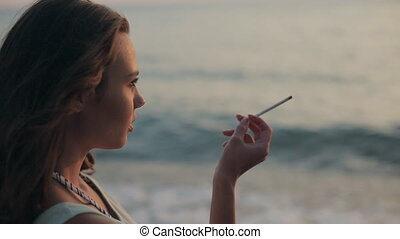 Girl smoking a cigarette at sunset near the sea