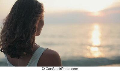 Beautiful woman smoking a cigarette at sunset near the sea -...