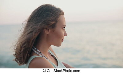 Curious woman looking on the sea with pleasure at sunset -...