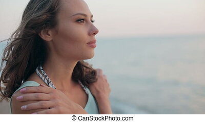 Thoughtful and beautiful girl standing near sea at sunset...