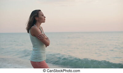 Harmonious girl standing near the sea at the sunset and...