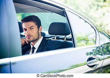 Businessman looking at window in car