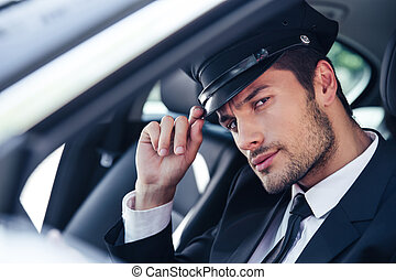 Handsome male chauffeur sitting in a car - Portrait of a...