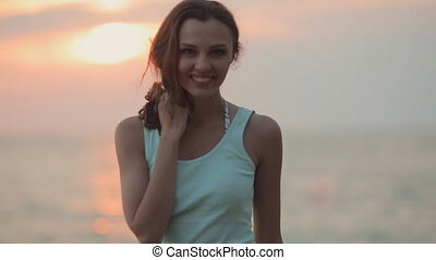 Amazing girl admiring the magnificent sunset on a beach -...