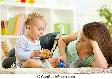 child and his mom play zoo holding animal toys