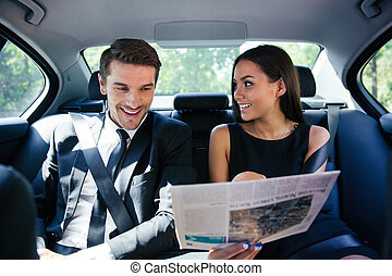 Couple reading newspaper in car - Happy couple reading...
