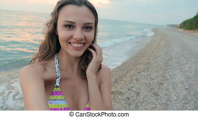 Lovely girl dressed in a swimsuit shoots herself on camera gopro near the sea