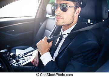 Male chauffeur sitting in a car