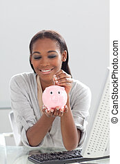 Afro-american businesswoman saving money in a piggybank at...