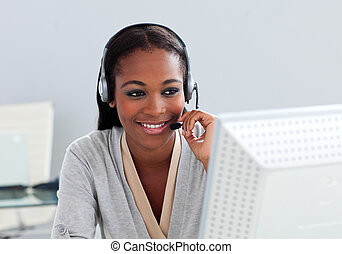 Assertive ethnic customer service agent with headset on at...