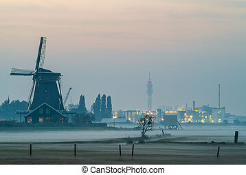 Dutch historic windmill with industry buildings in the background