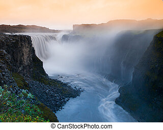 Godafoss waterfall in misty veil illuminated by sunset,...
