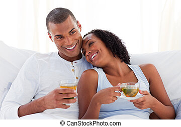 Merry ethnic couple drinking a cup of tea on their bed