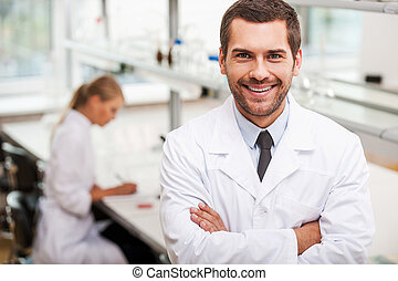 Confident scientist Happy young male scientist keeping arms...