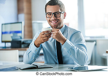 Coffee break. Cheerful young businessman in formalwear holding cup of coffeeand looking at camera while sitting at his working place