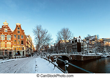 Snow has fallen in Amsterdam; the streets are covered with...