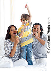 Animated family singing with microphones on a bed