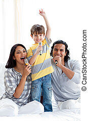 Joyful family singing with microphones on a bed