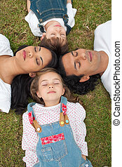 Merry family sleeping lying on the grass in a park