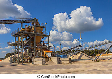 Sand sorting installation under blue clouded sky