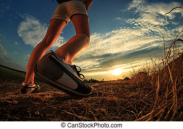 close up of feet sportwoman in autumn grass - Close up of...