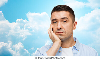 bored man face over blue sky and clouds background