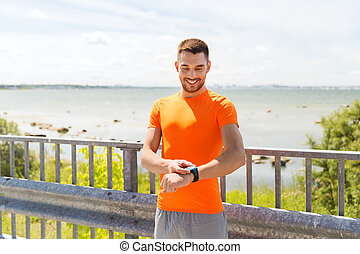 smiling young man with smart wristwatch at seaside -...