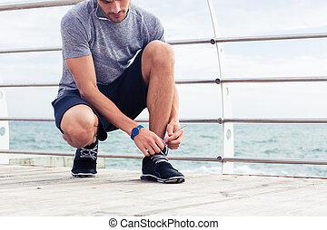 Man tie shoelaces outdoors - Portrait of a sports man tie...