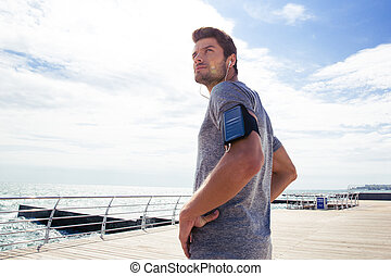 Thoughtful sports man standing outdoors
