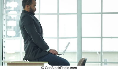 Young businessman tired straightens his shoulders and lays...